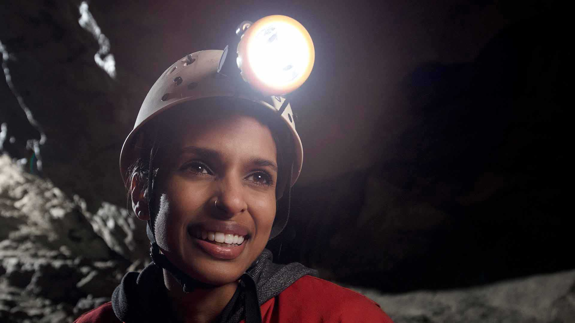 Happy female caver on the Explorer Tour wearing a helmet, light and coveralls.